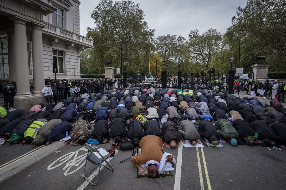 British Muslims pray before protesting outside French embassy in London after Macron defends Prophet Mohammed cartoons